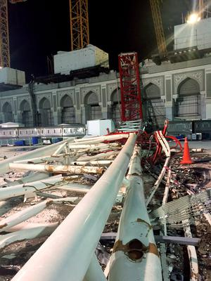 A construction crane is seen collapsed over the Grand Mosque, in Mecca, Saudi Arabia, early Saturday morning, Sept. 12, 2015.  The towering construction crane toppled over on Friday during a violent rainstorm in the Saudi city of Mecca, Islam's holiest site, crashing into the Grand Mosque and killing over a hundred people, ahead of the start of the annual hajj pilgrimage later this month. (AP Photo)