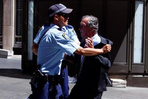 Police push back a member of the public who tried to get into a building located near the Lindt cafe, where hostages are being held, at Martin Place in central Sydney. Reuters/David Gray