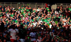 Fans shield their eyes from the sun during the match Niall Carson/PA Wire