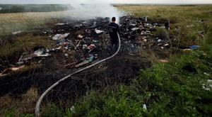 An emergency worker puts fires out at the Malaysia MH17 crash site