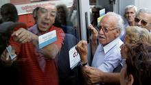 Pensioners waiting outside a closed National Bank branch and hoping to get their pensions, argue with a bank employee (L) in Iraklio on the island of Crete, Greece    REUTERS/Stefanos Rapanis
