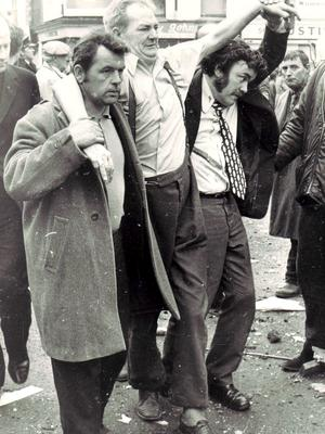 Passers-by help a victim of the Talbot Street bombing in 1974