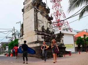 Foreign tourists past in front a tower warning of tsunami in Kuta near Denpasar, on Indonesia's resort island of Bali on March 22, 2017.     / AFP PHOTO / SONNY TUMBELAKASONNY TUMBELAKA/AFP/Getty Images