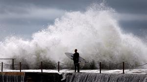 A surfer waits for a break in crashing waves before diving in for a surf off Sydney's Collaroy Beach