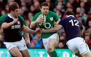Brian O'Driscoll (C) is challenged by Scotland's Duncan Taylor on Sunday