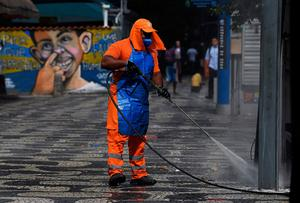 A council worker disinfects the entrance to a metro station as a prevention measure against the spread of the coronavirus in Rio de Janeiro, Brazil (Photo by Carl DE SOUZA / AFP) (Photo by CARL DE SOUZA/AFP via Getty Images)