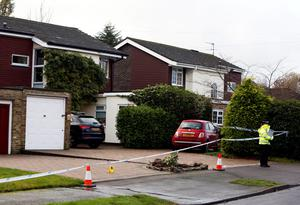 Police at the scene in Fetcham, Surrey, as murder squad detectives launched a manhunt after the bodies of a man and a woman were found at a property in Fetcham.