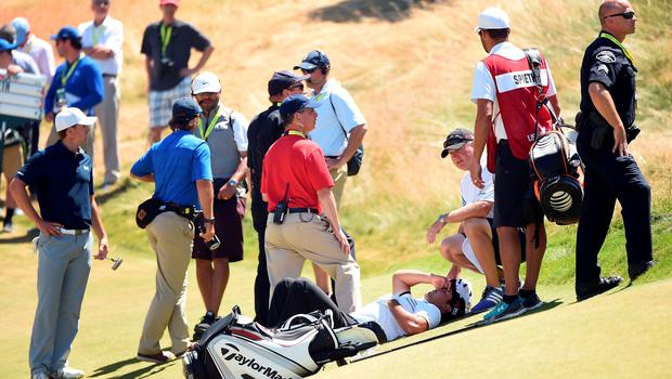 Jason Day is tended to by caddie Colin Swatton after collapsing due to dizziness. The Australian was able to finish out his round