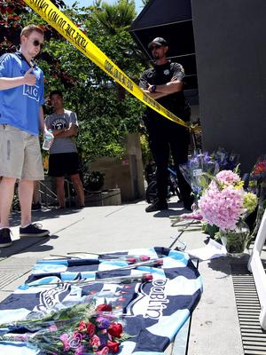 A man makes the sign of the cross over his heart after laying a bouquet of flowers near the scene of a 4th-story apartment building balcony collapse in Berkeley, California June 16, 2015.