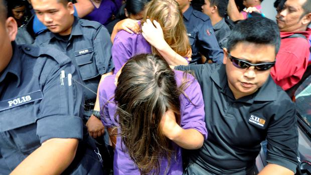 British national Eleanor Hawkins (front) is escorted by police as they leave a court hearing in Kota Kinabalu, in Malaysia