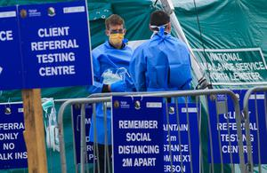 Reminder: Staff at the testing area for Covid-19 at Sir John Rogerson's Quay, Dublin, with signs reminding people to keep apart. Photo: Gareth Chaney, Collins