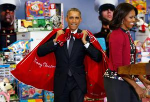 U.S. First Lady Michelle Obama smiles as President Barack Obama arrives with sacks of toys and gifts to donate to the Marine Corps Toys for Tots Campaign in Washington.  REUTERS/Kevin Lamarque