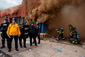 Police stand by a CVS that was on fire as firefighters arrive to fight the blaze, during a protest for the death of Freddie Gray in Baltimore, Maryland. Photo: EPA