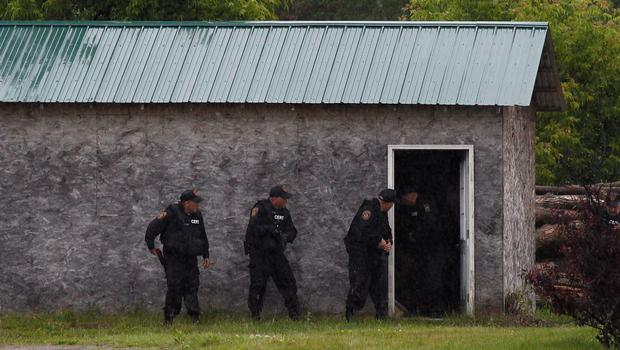 Law enforcement officers search a building on a farm near Willsboro, New York June 9, 2015. REUTERS/Chris Wattie