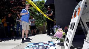 A man makes the sign of the cross over his heart after laying a bouquet of flowers near the scene of a 4th-story apartment building balcony collapse in Berkeley, California June 16, 2015. Six people were killed, including five young Irish citizens, and at least seven other people were injured when an apartment balcony collapsed early on Tuesday in the Californian city of Berkeley, Ireland's foreign minister said.  REUTERS/Elijah Nouvelage