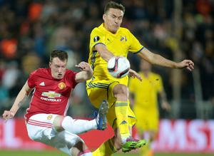 Manchester United's Phil Jones, left, and Rostov's Aleksandr Bukharov fight for the ball during the Europa League round of 16 first leg soccer match between Rostov and Manchester United in Rostov-on-Don, Russia, Thursday, March 9, 2017. (AP Photo/Denis Tyrin)