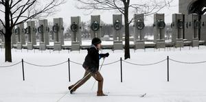 A woman skis past the World War II Memorial in Washington
