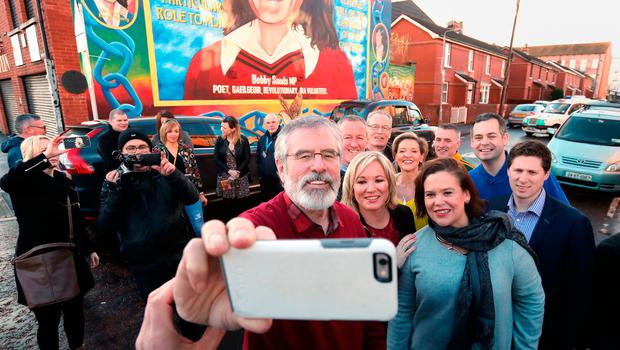 Closing the gap: Leader of Sinn Fein in the North, Michelle O'Neill, (centre) with Sinn Fien President Gerry Adams (centre left) and deputy leader Mary Lou McDonald taking a selfie outside their HQ in Belfast after last week's election