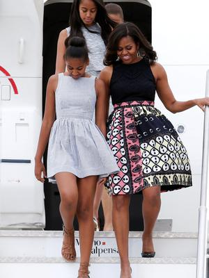 U.S. first lady Michelle Obama (R) arrives with her daughters Sasha (L) and Malia (top) at Malpensa airport in Milan, Italy, as part of her European trip June 17, 2015.  REUTERS/Alessandro Garofalo