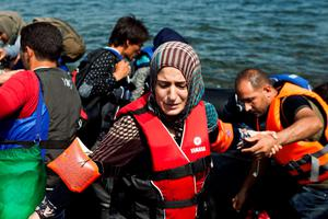 A Syrian refugee wearing a life jacket and armbands reacts moments after arriving on a dinghy on the Greek island of Lesbos, September 7, 2015. Reuters/Dimitris Michalakis