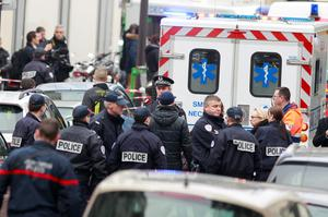 Police officers arrive at the scene after gunmen stormed a French newspaper, killing at least 12 people, in Paris, France. (AP Photo/Remy de la Mauviniere)