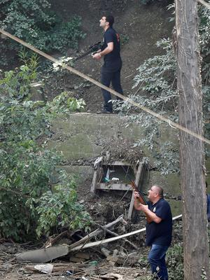 Armed municipality workers search for a white tiger that escaped when floods destroyed its enclosure, in Tbilisi, Georgia, June 17, 2015. Tigers, lions, bears and wolves were among more than 30 animals that escaped from a Georgian zoo and onto the streets of the capital Tbilisi on Sunday during floods that killed at least 12 people. REUTERS/David Mdzinarishvili