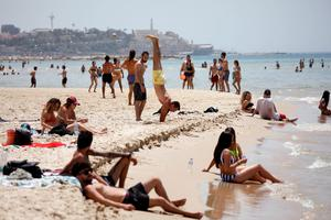People visit a beach along the coast of the Mediterranean Sea during a heatwave in Israel as restrictions following the coronavirus disease (COVID-19) ease around the country, in Tel Aviv, Israel May 17, 2020. REUTERS/Amir Cohen
