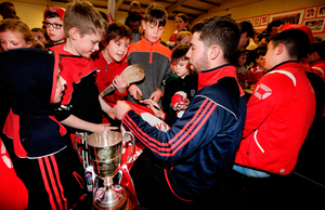 Left: Local children welcome home the Cuala hurling champions and crowd around Oisín Gough for an autograph at their clubhouse in Dalkey, Dublin. Photos: Steve Humphreys