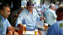 A bartender wearing a face shield serves beer on a table outside a pub in Cologne, Germany. REUTERS/Thilo Schmuelgen