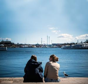 A DIFFERENT APPROACH: Two women enjoy the spring weather as they sit at Nybroplan in Stockholm during the coronavirus Covid-19 pandemic. Picture: AFP/Getty