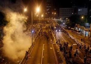 Riot police fire teargas to disperse protesters as a fire engine tries to enter after thousands of demonstrators blocked the main street to the financial Central district outside the government headquarters in Hong Kong September 29, 2014