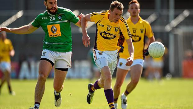 Kevin O'Grady, Wexford, in action against Lorcan Smith, Westmeath