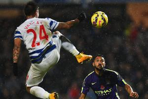 Eduardo Vargas of QPR jumps for the ball against Gael Clichy. Photo credit: Tom Dulat/Getty Images