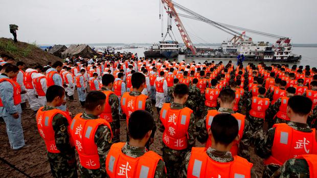Rescuers bow during a commemoration service near the raised ship Eastern Star on the Yangtze River in Jianli county of southern Chinas Hubei province Sunday, June 7, 2015.  (AP Photo/Andy Wong)