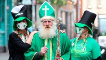 Two women in face masks take a picture with a man dressed as St Patrick near the Temple bar in Dublin, on St Patrick's day.: Niall Carson/PA Wire
