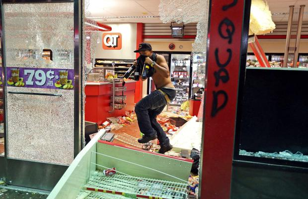 A man leaves a store on Sunday, Aug. 10, 2014, in Ferguson, Mo. A few thousand people crammed a suburban St. Louis street Sunday night at a vigil for unarmed 18-year-old Michael Brown shot and killed by a police officer, while afterward several car windows were smashed and stores were looted as people carried away armloads of goods as witnessed by an an Associated Press reporter.