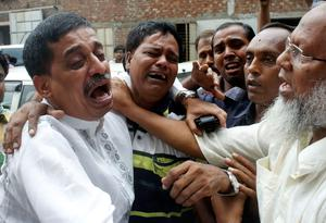 Company officials cry after a fire at a factory belonging to Tung Hai Group, a large garment exporter, in Dhaka May 9, 2013. Eight people were killed when the fire swept through the garment factory in an industrial district of the Bangladeshi capital Dhaka, police and an industry association official said on Thursday. REUTERS/Andrew Biraj (BANGLADESH - Tags: DISASTER BUSINESS TEXTILE)