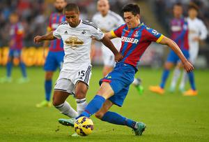 Swansea City's Wayne Routledge is tackled by Crystal Palace defender Martin Kelly during their Premier League clash at the Liberty Stadium. Photo: Mike Hewitt/Getty Images