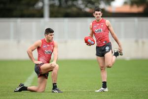 Lewis Melican and Colin O'Riordan look on during a Sydney Swans AFL training session at Lakeside Oval last July. Photo: Jason McCawley/Getty Images