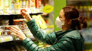 Vienna: A shopper scans the shelves while wearing a protective face mask. Figures show that supermarkets do not appear to be breeding grounds for the virus. PIC: REUTERS/Leonhard Foeger...I