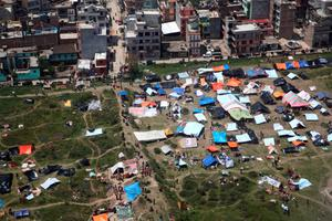 Tents are set up in an open area near multi-storey buildings following an earthquake in Kathmandu, Nepal in this Red Cross handout picture taken on April 27, 2015.  REUTERS/IFRC/Palani Mohan/Handout via Reuters
