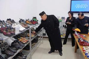 North Korean leader Kim Jong Un (L) provides field guidance to the Ryuwon Shoes Factory in this undated photo released by North Korea's Korean Central News Agency