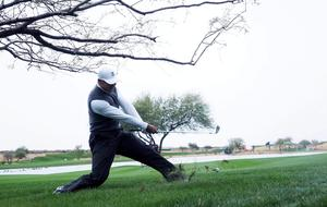 Tiger Woods plays from the rough of the 11th