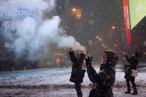 Female tourists use their smart phones to capture a snow storm in Times Square, New York early morning January 27, 2015.  REUTERS/Adrees Latif