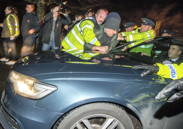 Gardai attempt to remove a water protester from the bonnet of the car carrying Taoiseach Enda Kenny after demonstrators surrounded him as he arrived at a function in Sligo last night. Photo: James Connolly.