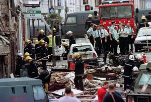Police officers and firefighters inspecting the damage caused by a bomb explosion in Market Street, Omagh, in 1998 (Paul McErlane/PA)