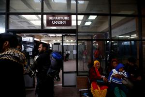 Tourists stand in front of the Departure gate of Tribhuvan International Airport as they wait for their flight after an earthquake in Kathmandu, Nepal April 28, 2015. REUTERS/Navesh Chitrakar