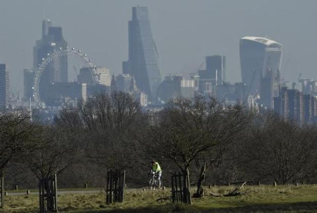 A cyclist rides through Richmond Park, with the City of London financial district seen behind in London, Britain February 19, 2016. REUTERS/Toby Melville