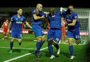 AFC Wimbledon's Adebayo Akinfenwa (2nd R) celebrates with team-mates after scoring a goal during their FA Cup third round soccer match against Liverpool at Kingsmeadow Stadium