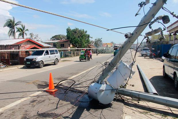 Motorists speed past a fallen electric pylon damaged at the height of Typhoon Phanfone in Balasan town in Iloilo province on December 26, 2019. (Photo by STR / AFP) (Photo by STR/AFP via Getty Images)